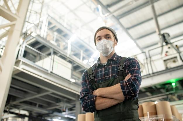 Junge ernsthafte männliche arbeiter einer großen fabrik in arbeitskleidung und schutzmaske, die mit verschränkten armen vor der kamera im lager steht