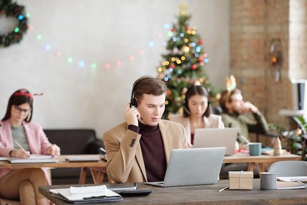 Junge ernsthafte männliche kundenbetreuer mit headset, die auf das laptop-display schauen, während sie am schreibtisch sitzen und kunden beraten