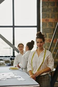Junge ernsthafte näherin mit maßband am hals, die in der werkstatt mit ihren kollegen am tisch steht und ideen in der nähe bespricht