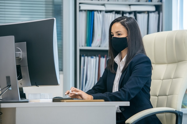Junge ernsthafte sekretärin, die während des netzwerks auf den computerbildschirm schaut