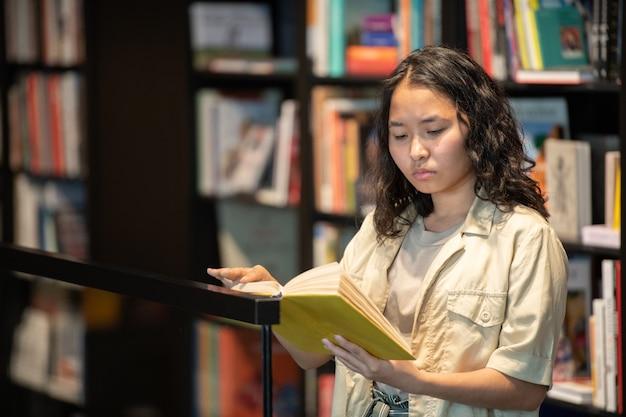 Junge ernsthafte studentin liest ein buch, während sie am großen bücherregal steht