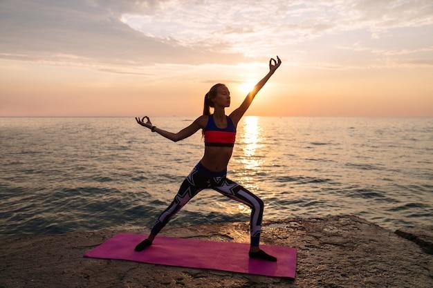 Junge erstaunliche frau, die auf dem strand, übendes yoga bei schönem sonnenaufgang trainiert.