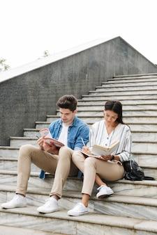 Junge erstaunliche konzentrierte liebevolle paar studentenkollegen im freien draußen auf stufen lesen buch schreiben notizen studieren.