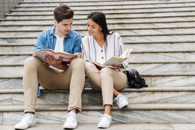 Junge erstaunliche liebevolle paar studentenkollegen im freien draußen auf stufen lesen buch schreiben notizen studieren.
