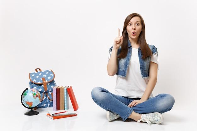 Junge erstaunliche studentin, erleuchtet mit neuen gedanken, idee, die mit dem zeigefinger nach oben zeigt, sitzt in der nähe von globus-rucksack-schulbüchern