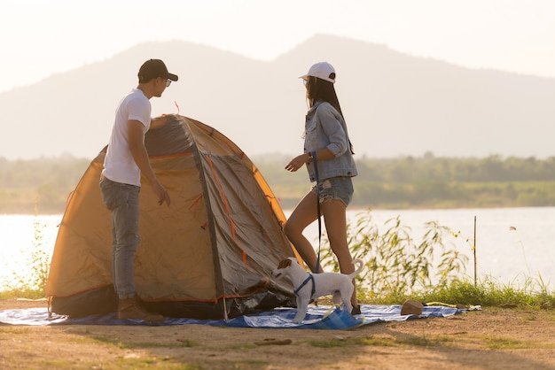 Junge erwachsene asiatische paare schlagen auf und bauen zelt für camping um den see auf.