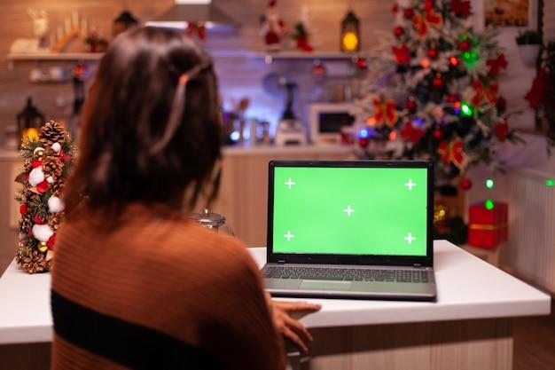 Junge erwachsene beobachten laptop-gerät mit grünem bildschirm