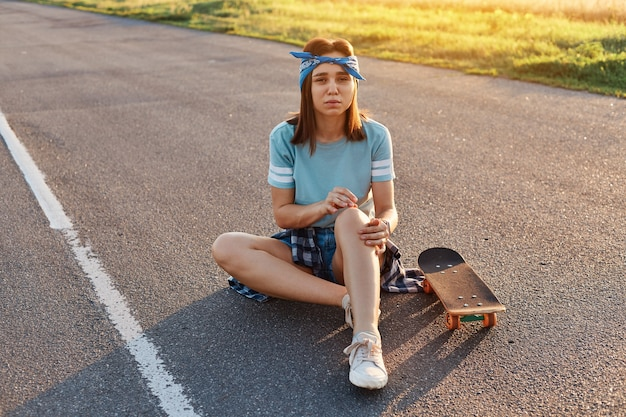 Junge erwachsene brünette frau, die auf asphaltstraße sitzt und ein trauma hat, nachdem sie vom skate heruntergefallen ist, knieschmerzen hat und die kamera mit stirnrunzelndem gesicht betrachtet