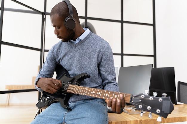 Junge erwachsene, die gitarre spielen