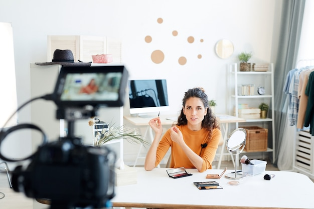 Junge erwachsene frau, die alleine in ihrem zimmer sitzt und neues video für ihren beauty-blog-kanal dreht