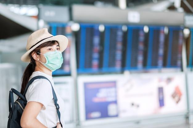 Junge erwachsene frau, die chirurgische maske im flughafenterminal trägt