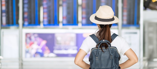 Junge erwachsene frau, die gesichtsmaske im flughafenterminal trägt, schutz coronavirus-krankheit-infektion