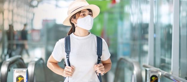 Junge erwachsene frau, die gesichtsmaske im flughafenterminal trägt