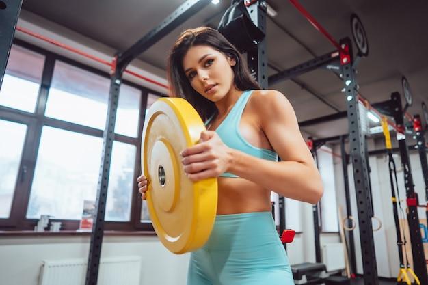 Junge erwachsene frau, die kraftübungen im fitnessstudio tut