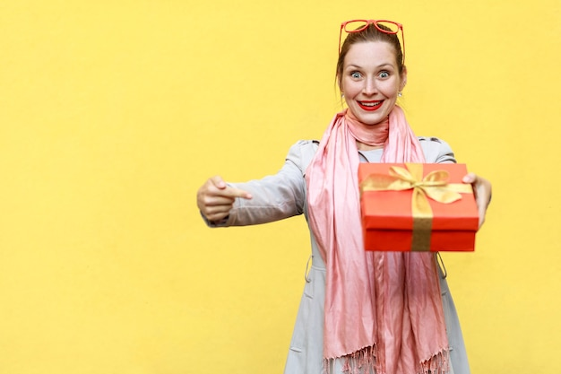 Junge erwachsene frau, die mit dem finger auf die geschenkbox zeigt und die kamera und das zahnige lächeln betrachtet