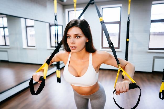 Junge erwachsene frau, die übungen im fitnessstudio macht