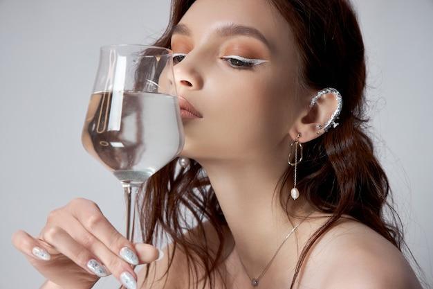 Junge erwachsene frau hält ein glas wasser in ihrer hand nahe gesicht. schönes make-up, saubere haut