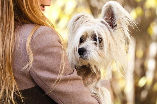 Junge erwachsene frau hält einen hund auf ihrer schulter. frau drehte sich um