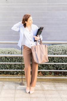 Junge erwachsene frau lächelnd schöne geschäftsfrau, die auf der straße auf einen kunden mit laptop und ordner wartet. erfolgreiches geschäftsfrauenkonzept. platz kopieren