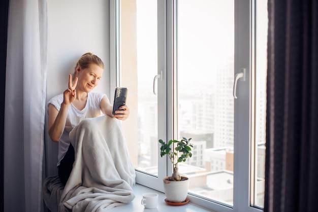 Junge erwachsene frau mit brille macht ein selfie, das zu hause auf der fensterbank sitzt und mit der hand gestikuliert. frau lächelt beim chatten und schaut auf das smartphone.