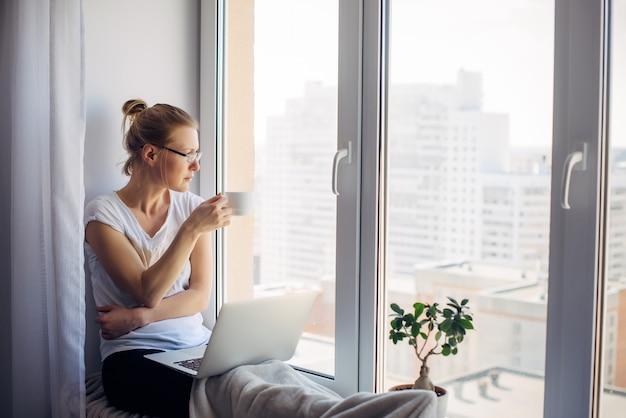 Junge erwachsene frau mit brille und weißem t-shirt sitzt auf der fensterbank mit laptop zu hause, trinkt kaffee und schaut auf das fenster. remote-arbeit, freiberuflich, quarantäne, selbstisolation, sperrung.