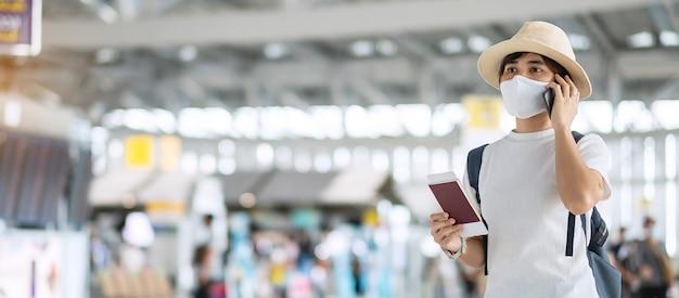 Junge erwachsene frau mit gesichtsmaske, die pass und smartphone im flughafen hält