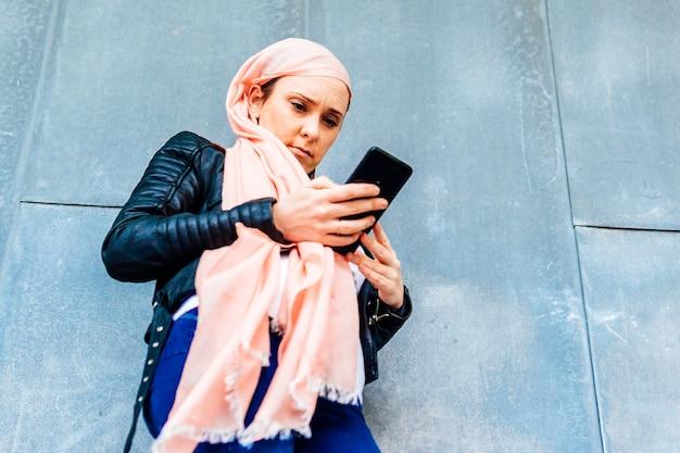 Junge erwachsene frau mit rosa kopftuch gegen krebs, die medizinische ergebnisse auf dem smartphone betrachtet. krebskonzept mittleren alters
