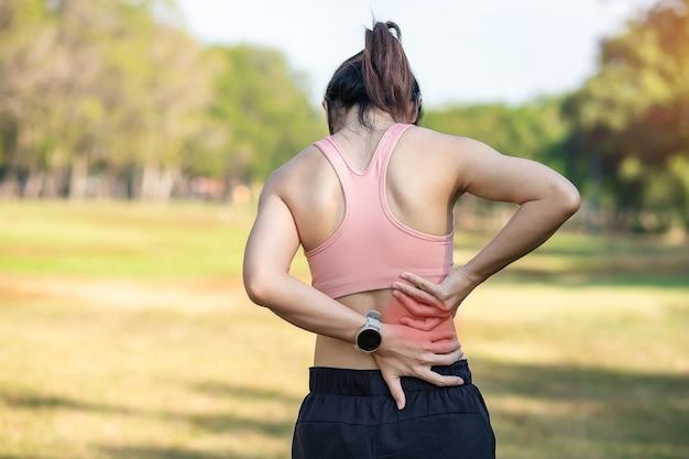 Junge erwachsene frau mit seinen muskelschmerzen während des laufens.