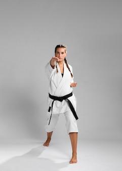 Junge erwachsene frau mit trainingskarate des kämpfers des schwarzen gürtels