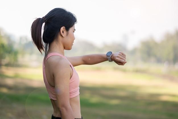 Junge erwachsene frau prüft zeit und cardio-herzfrequenz auf sport-smartwatch während des laufens im park im freien, läuferfrau, die am morgen joggt. bewegung, technologie, lebensstil und training
