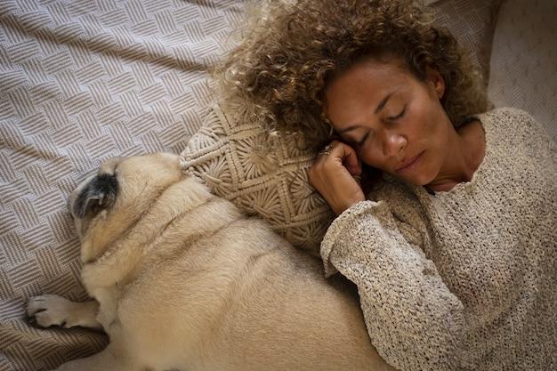 Junge erwachsene frau schläft zu hause im bett mit ihrem mopshund zusammen auf dem bett. müde frau mit hund auf dem bett liegend. draufsicht einer müden frau, die mit ihrem hund auf einem gemütlichen bett zu hause schläft