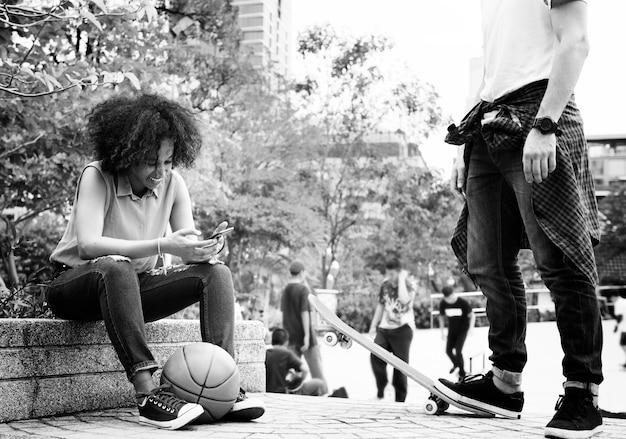Junge erwachsene freunde, die am park unter verwendung der smartphones kühlen und skateboard fahren