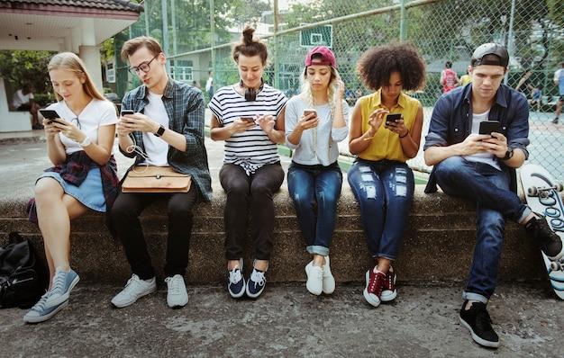 Junge erwachsene freunde, die zusammen draußen jugendkulturkonzept der smartphones verwenden