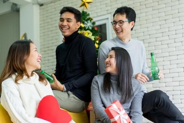 Junge erwachsene freunde, die zusammen im wohnzimmer sprechen und lachen, verzierten für frohe weihnachten der partei