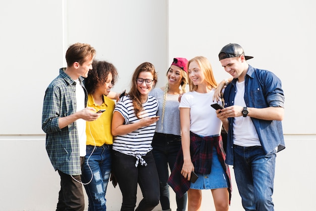 Junge erwachsene freunde, die zusammen jugendkulturkonzept der smartphones draußen verwenden