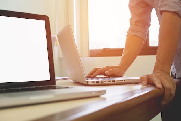 Junge erwachsene geschäftsmann eingabe mit laptop im büro