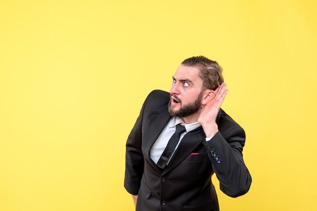 Junge erwachsene hören geheimnis vorsichtig über gelb stehen