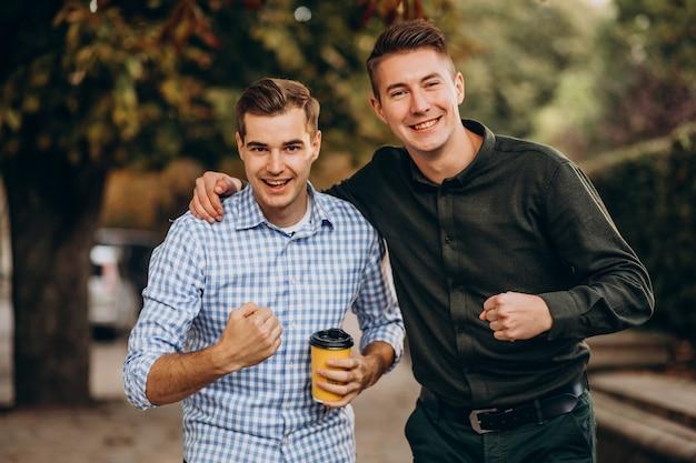 Junge erwachsene jungs, die zusammen im park gehen