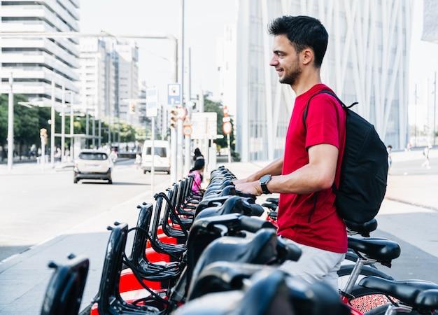 Junge erwachsene kaukasische studentin, die ein gemietetes fahrrad nimmt