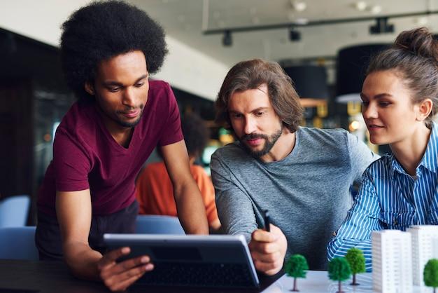 Junge erwachsene kollegen, die mit technologie arbeiten