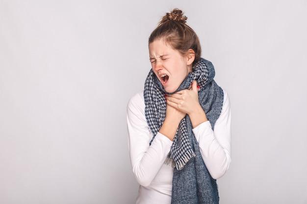 Junge erwachsene kranke frau, die ihren hals berührt, husten, halsschmerzen hat. studioaufnahme