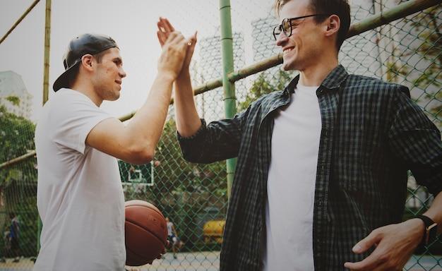 Junge erwachsene männliche freunde, die basketball im park spielen