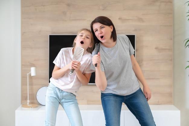 Junge erwachsene mutter der glücklichen familie und niedliche jugendlich tochter, die spaß haben, karaoke-lied in haarbürsten zu singen. mutter lacht und genießt lustige lifestyle-aktivitäten mit teenager-mädchen zu hause zusammen.