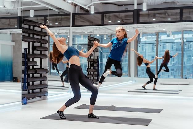 Junge erwachsene mutter, die fitness mit ihrer kleinen tochter tut