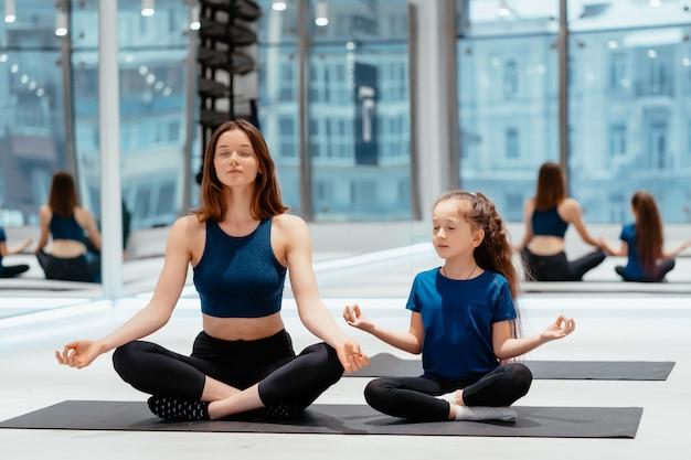 Junge erwachsene mutter und kleine tochter, die zusammen yoga praktizieren