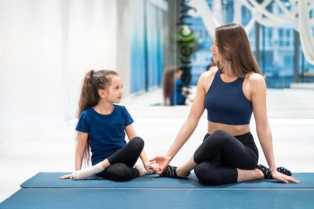 Junge erwachsene mutter und kleine tochter zusammen auf aerobic