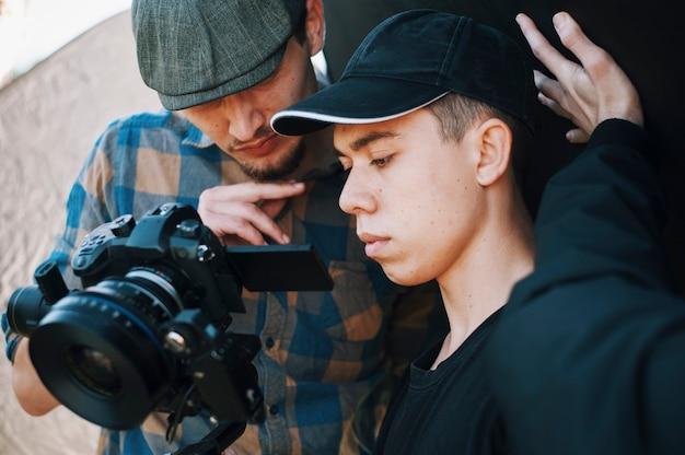 Junge erwachsene operator und regisseur fotografieren vor der kamera. konzentrierte sehenswürdigkeiten im sucher