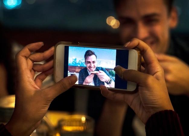 Junge erwachsene paare an einem abendessen nehmen smartphonefotos