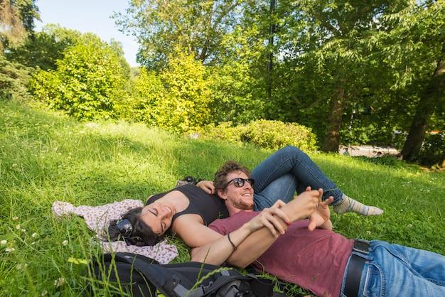 Junge erwachsene paare, die sich auf üppigem grünem gras im park, entspannend hinlegen und umfassen