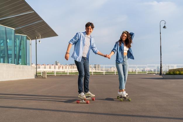 Junge erwachsene reiten longboard auf der sommerstadtstraße hipster-paar auf skateboards im stadtgebiet